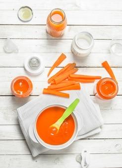 Cibo per neonato. purea di carote baby con latte in bottiglia. su una superficie di legno bianca.