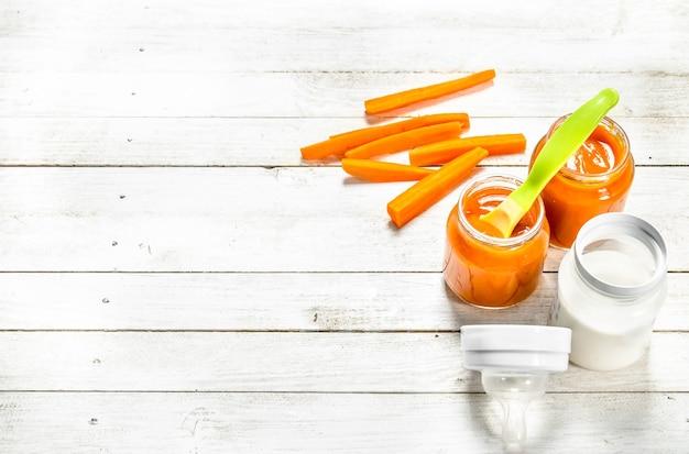 Cibo per neonato. purea di carote baby con latte in bottiglia. su un tavolo di legno bianco.