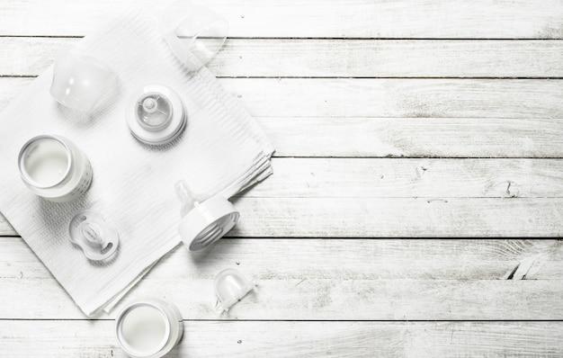 Cibo per neonato. latte per neonati in biberon. su un tavolo di legno bianco.