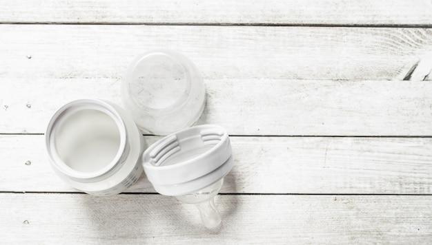 Alimenti per bambini latte per bambini in piccola bottiglia su un tavolo di legno bianco