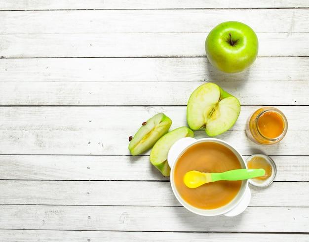 Cibo per neonato. purea di bambino di mele verdi fresche. su uno sfondo di legno bianco.