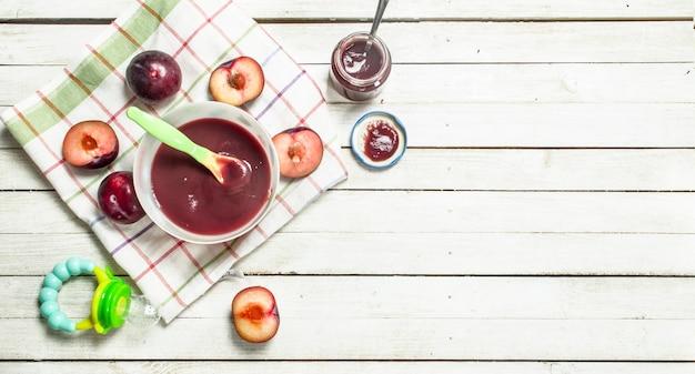 Alimenti per bambini purea di prugne fresche su uno sfondo di legno bianco