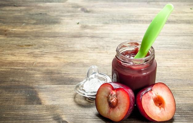 Alimenti per bambini purea di prugne fresche su uno sfondo di legno