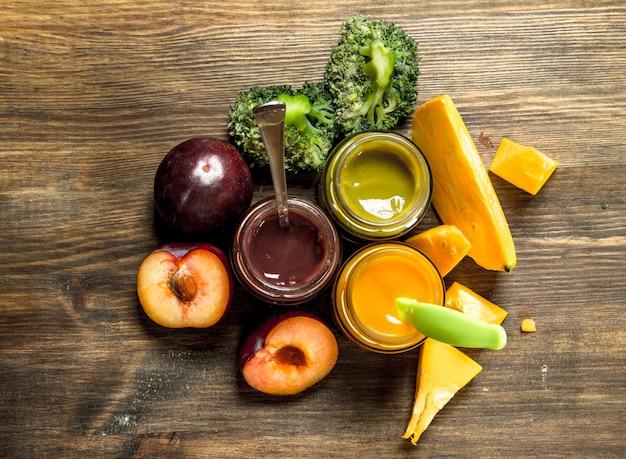 Cibo per neonato. varietà di purea di frutta e verdura per bambini. su uno sfondo di legno.