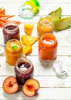 Cibo per neonato. varie puree per neonati di frutta e verdura fresca. su uno sfondo di legno bianco.