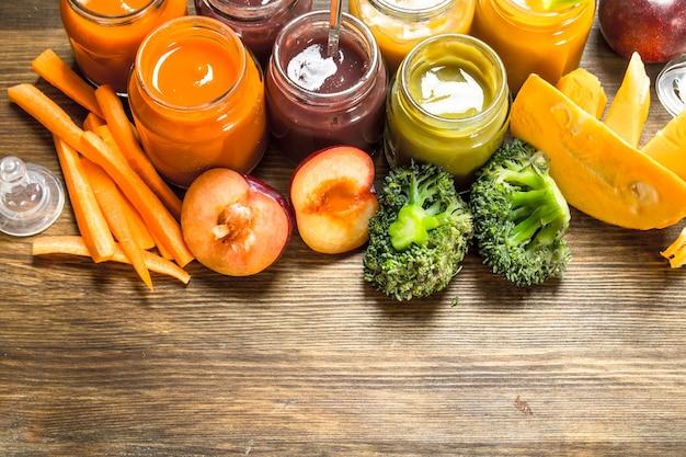 Cibo per neonato. varie puree di frutta e verdura. su uno sfondo di legno.
