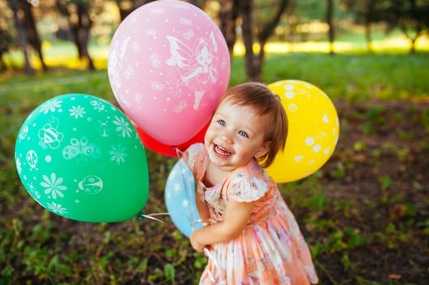 La neonata di 2-3 anni che tiene i palloni all'aperto. festa di compleanno. infanzia. felicità.