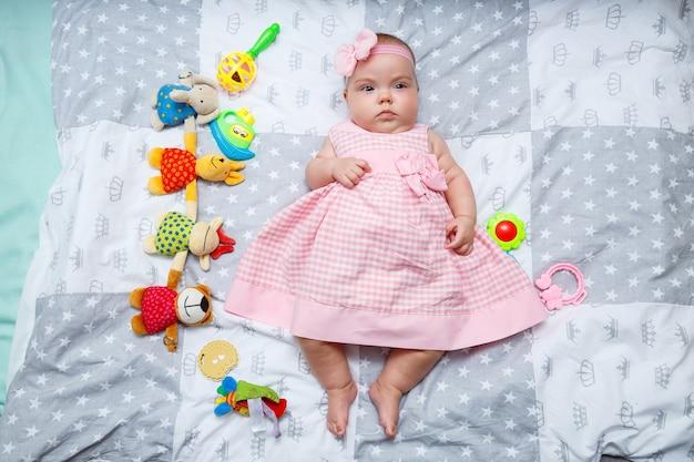La bambina di 3 mesi è sdraiata sul letto. bambino in un vestito rosa e una fascia in un pannolino