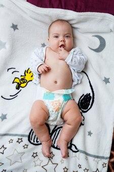 La bambina di 3 mesi è sdraiata sul letto. bambino senza vestiti in un pannolino
