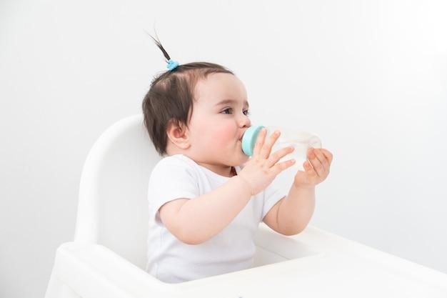 Neonata in sedia bambino acqua potabile dal biberon.