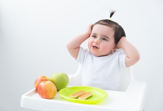 Neonata in seggiolone che mangia mele e biscotti. primo alimento solido per bambini.