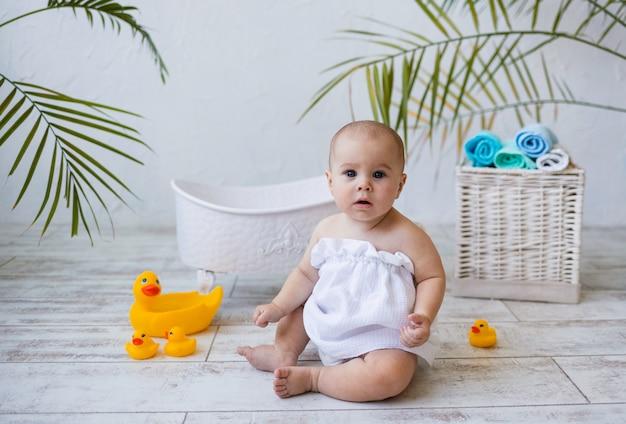 La bambina in un asciugamano da bagno è seduta vicino a un bagno bianco sul pavimento e guarda la telecamera