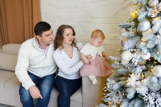 Neonata in un bel vestito rosa con i suoi genitori seduti vicino all'albero di natale con i regali