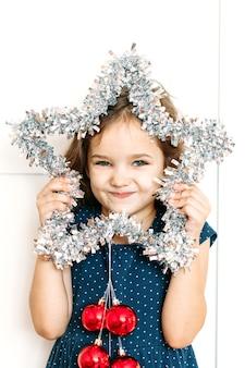 Neonata in vestito blu che tiene la stella della decorazione di natale del nuovo anno