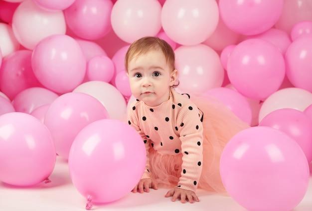 La neonata festeggia il suo primo compleanno. ragazza su sfondo di palloncini rosa. vista dall'alto