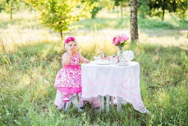 La bambina festeggia il suo primo compleanno con torta e palloncini in natura