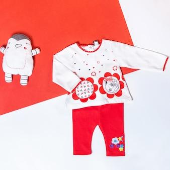 Vestiti della neonata e roba del giocattolo, concetto di moda del bambino