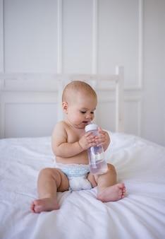 La bambina con il pannolino si siede sul letto e succhia una bottiglia d'acqua