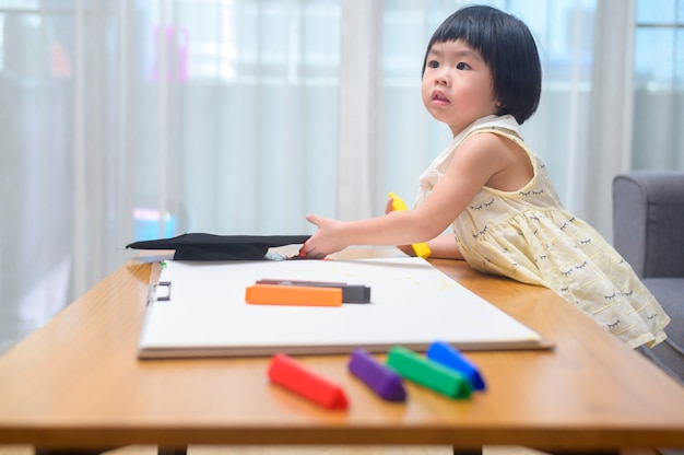 Disegno della neonata con matite colorate nel soggiorno di casa.