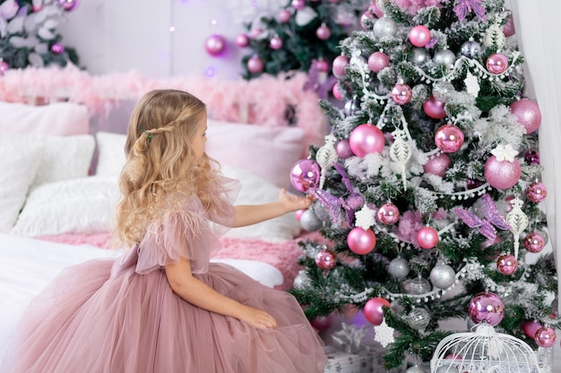 La neonata veste l'albero di natale con un bellissimo vestito rosa, il nuovo anno e il concetto di natale