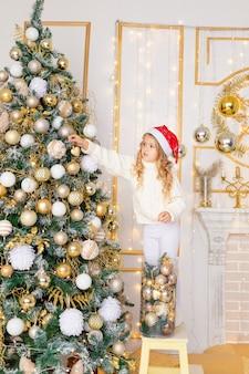La neonata veste l'albero di natale a casa, il nuovo anno e il concetto di natale