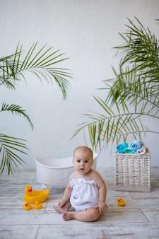 La bambina è seduta in un asciugamano da bagno vicino a un bagnetto con un giocattolo di anatra. orientamento verticale