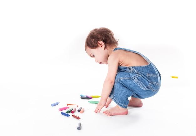 La bambina sta scrivendo qualcosa sul grande foglio, seduta su di esso