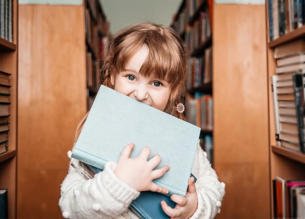 Bambina in biblioteca con libri in mano. bambino carino esplora gli scaffalihe