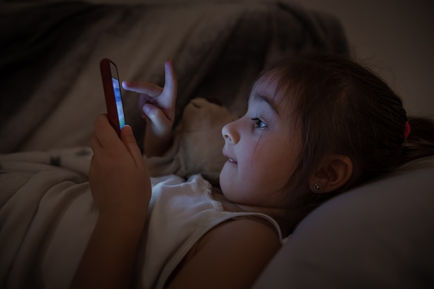 Una bambina giace a letto e utilizza uno smartphone da vicino. il concetto di dipendenza infantile da cartoni animati e giochi.