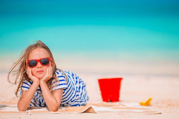 Neonata che fa castelli di sabbia e divertirsi in spiaggia tropicale