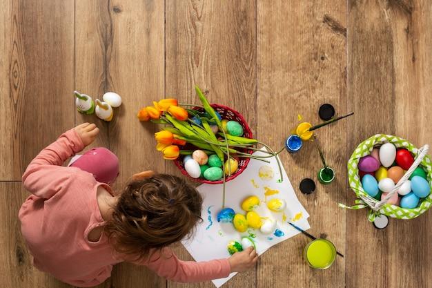 Neonata che dipinge le uova di pasqua a casa