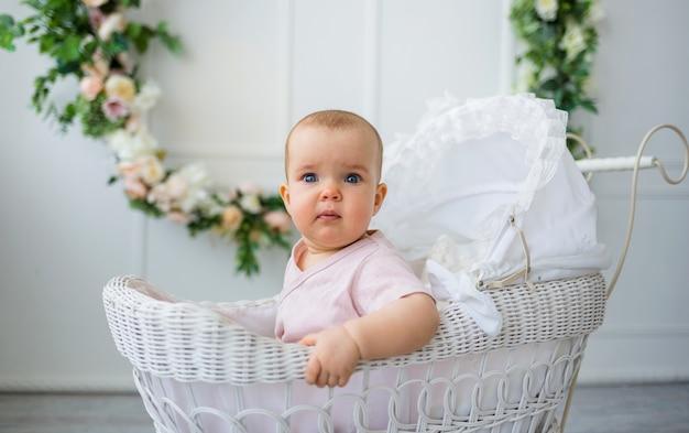 La neonata in una tuta rosa si siede in un passeggino retrò su bianco