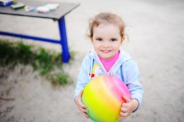 Neonata che gioca con una palla colorata nel parco giochi
