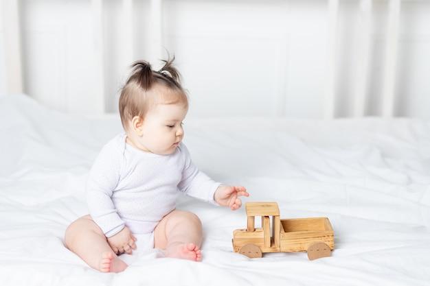 Neonata che gioca macchina da scrivere giocattolo di legno sul letto a casa, il concetto di gioco e sviluppo dei bambini