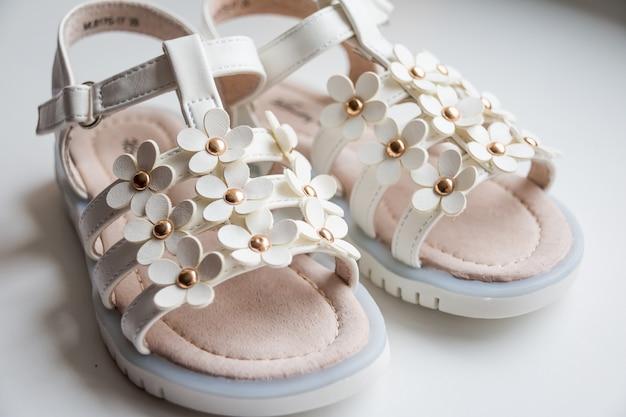 Sandali della neonata su fondo bianco