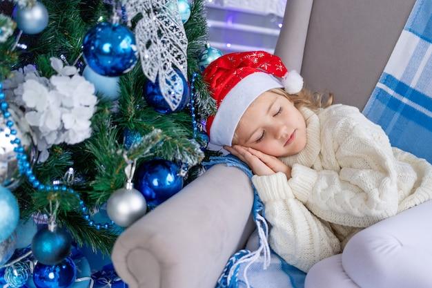 Bambina con il cappello di babbo natale che dorme vicino all'albero di natale, il concetto di nuovo anno e natale