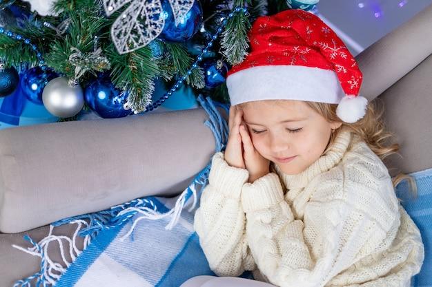 Neonata in cappello di babbo natale che dorme vicino all'albero di natale
