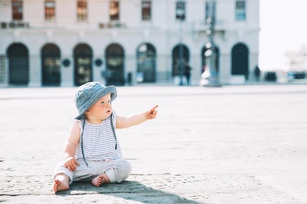 Bambina seduta su una strada di una città europea e dito puntato su piccolo bambino all'aperto in una città