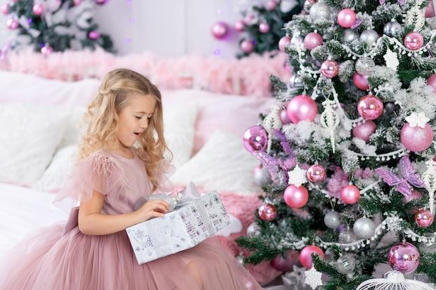 La bambina spacchetta un regalo di natale all'albero di natale in un bellissimo vestito di colore rosa, il concetto di capodanno e natale