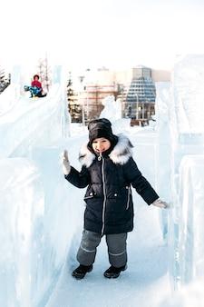 Bambina che cammina in inverno, sculture di ghiaccio invernali, cappello e giacca calda