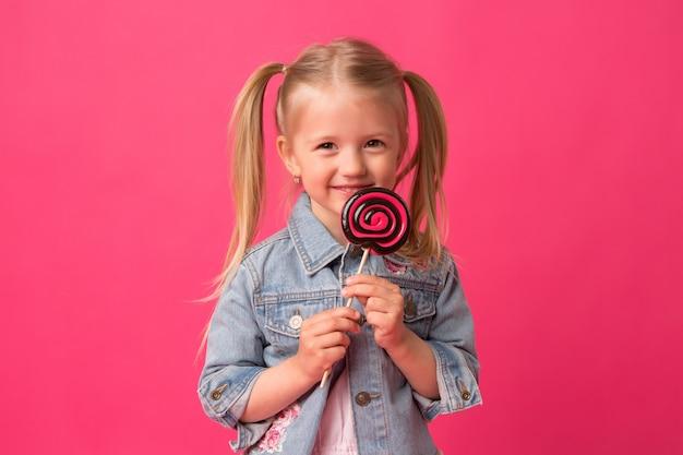 Bambina con lecca-lecca su sfondo rosa