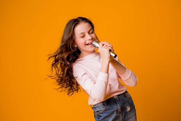Bambina con microfono sorridente cantando Foto Premium