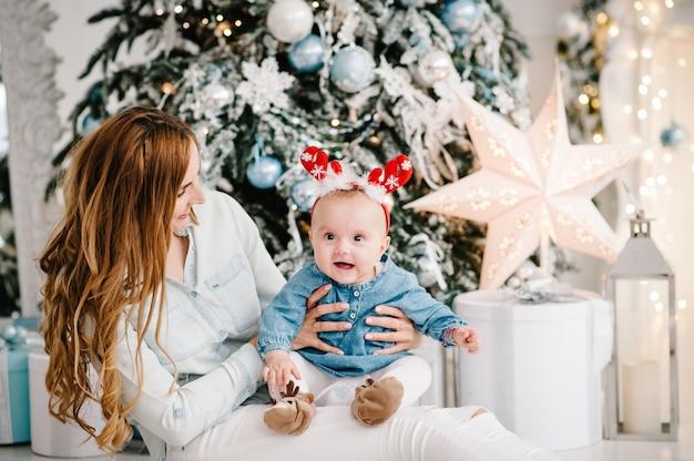 Neonata con la mamma sul pavimento vicino all'albero