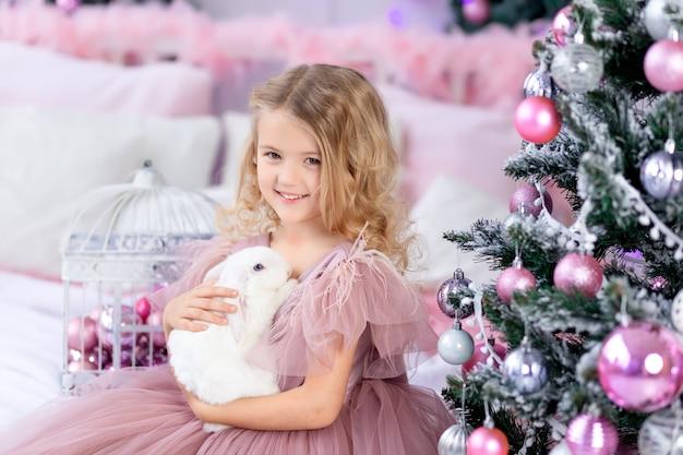 Neonata con coniglio all'albero di natale in un bellissimo vestito rosa, capodanno e concetto di natale
