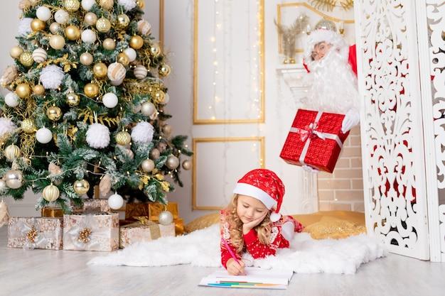 La bambina scrive una lettera e babbo natale con un regalo la spia all'albero di natale, il concetto di nuovo anno e natale