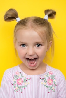 Bambina su giallo, mostra emozioni di sorpresa