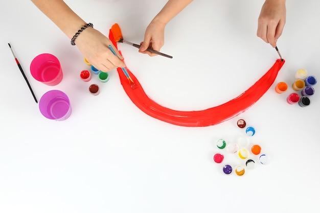 La mano del bambino dipinge un arcobaleno su uno sfondo bianco