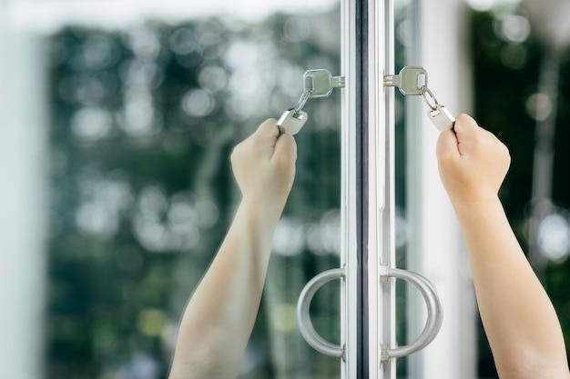 Mano del bambino che mette la chiave di casa nella serratura della porta d'ingresso della casa