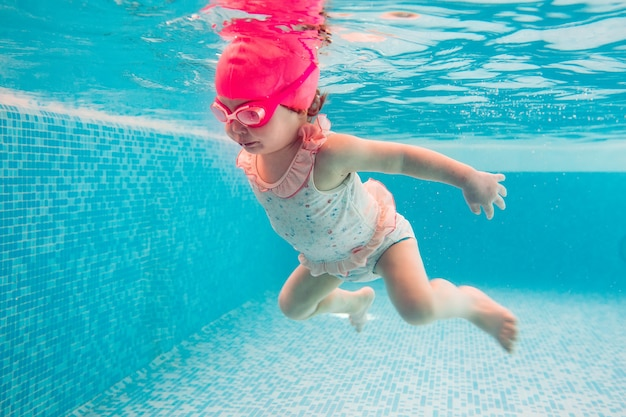Bambino. il bambino felice impara a nuotare, si tuffa sott'acqua con divertimento in piscina per tenersi in forma. diving.