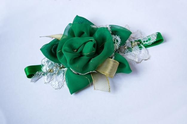 Fascia per capelli, fiore in tessuto e pizzo, perline su una superficie bianca